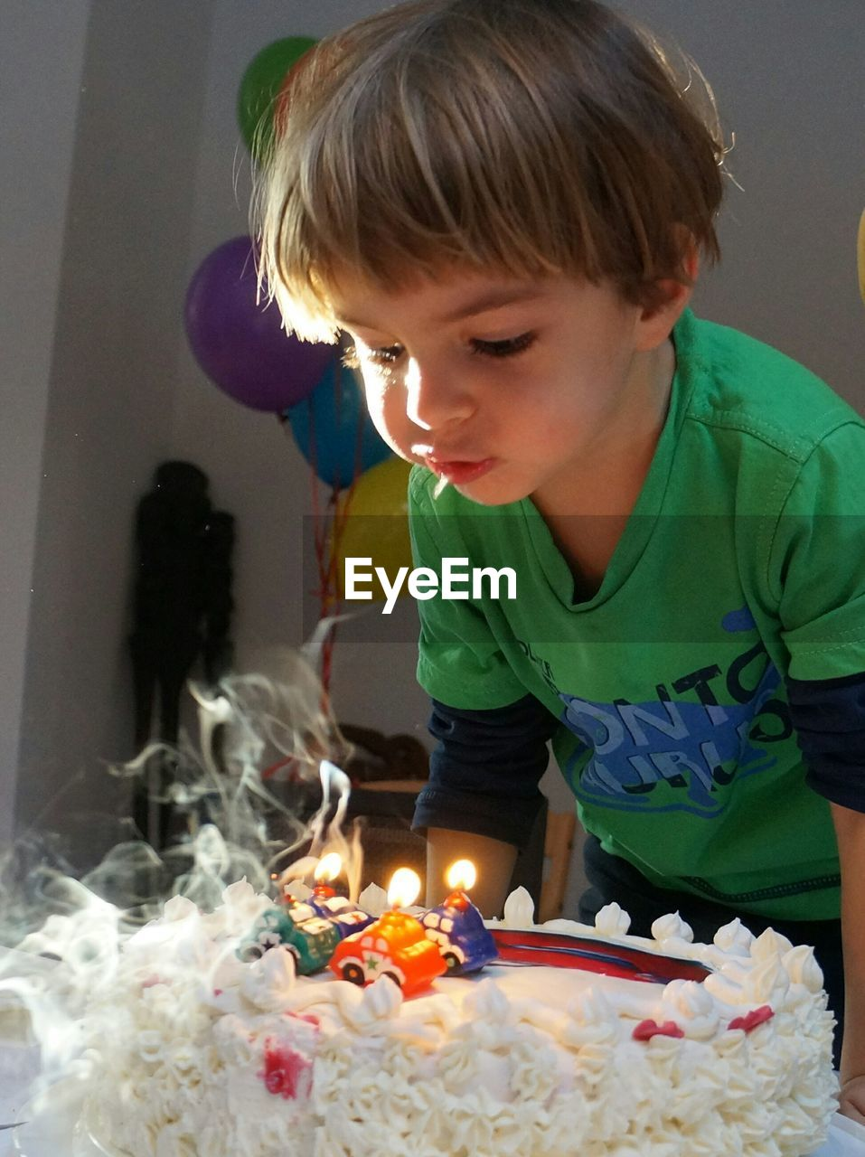 Boy Blowing Birthday Candles On Cake At Home