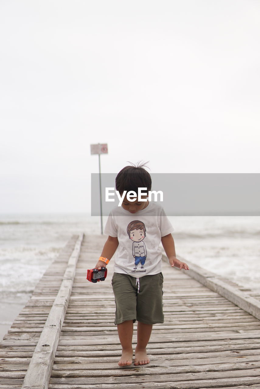 Boy looking down while walking on pier over sea against sky