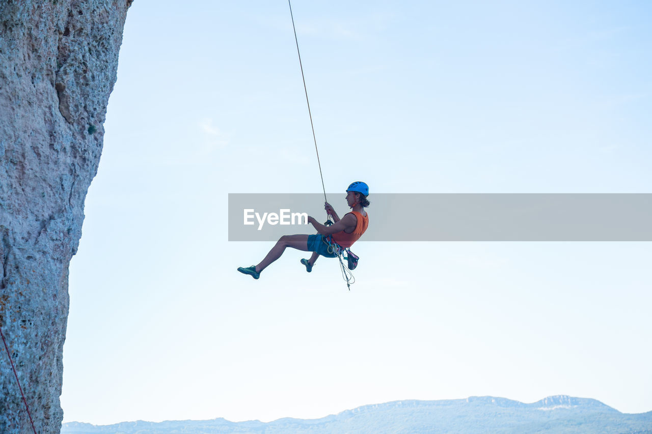 Low Angle View Of Man Handing On Rope By Rocky Mountain Against Clear Sky