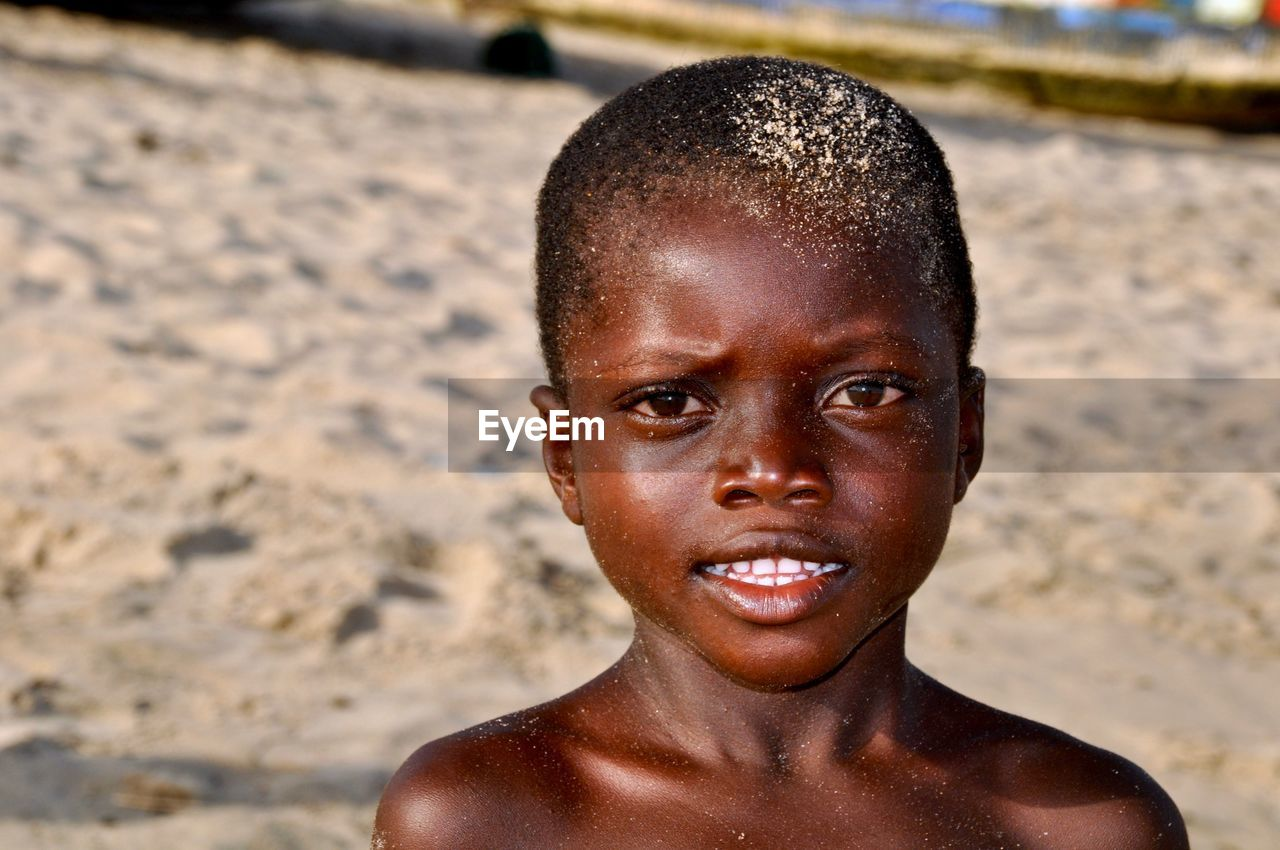 Close-up portrait of shirtless boy standing at beach