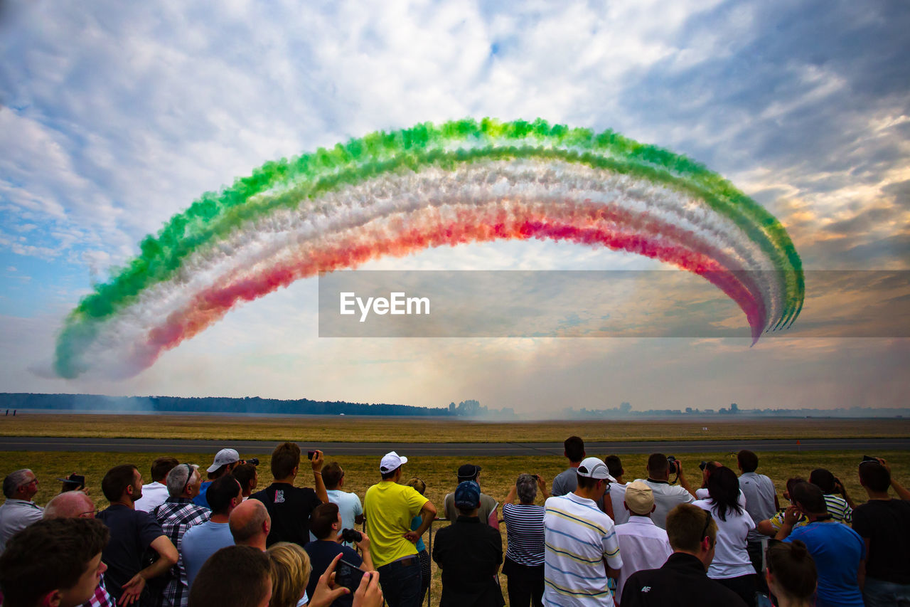 crowd, large group of people, real people, group of people, sky, cloud - sky, flying, motion, multi colored, men, nature, airplane, smoke - physical structure, airshow, women, rear view, air vehicle, lifestyles, travel, watching, outdoors, plane, vapor trail, spectator