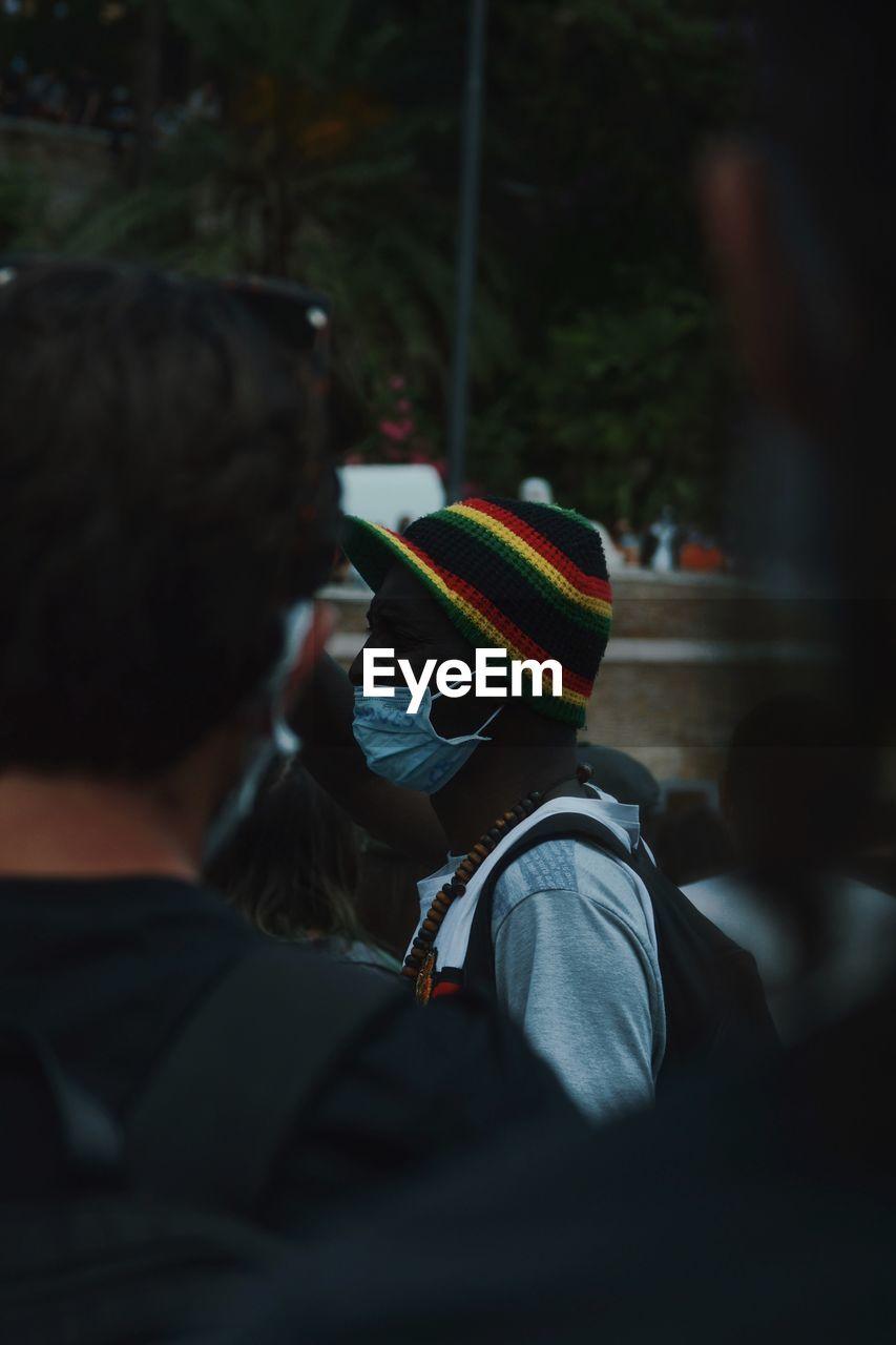 View of man wearing flu mask standing outdoors
