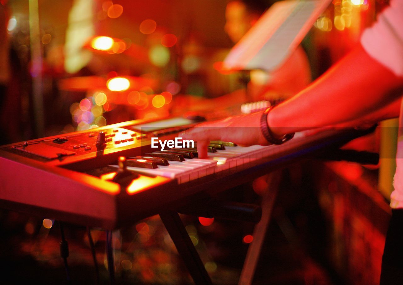Cropped hands of man playing piano in nightclub