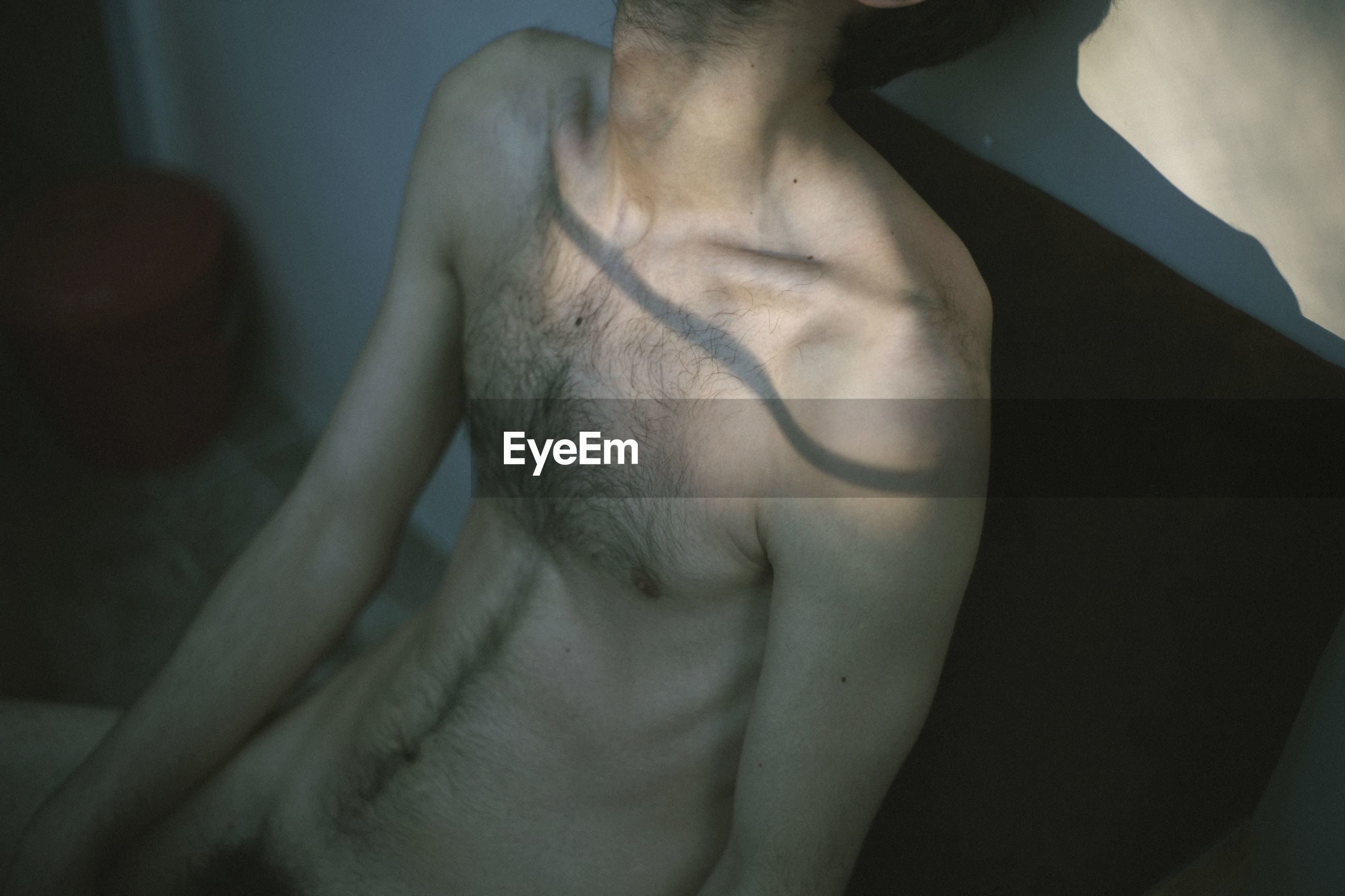 CLOSE-UP OF SHIRTLESS MAN STANDING IN BED