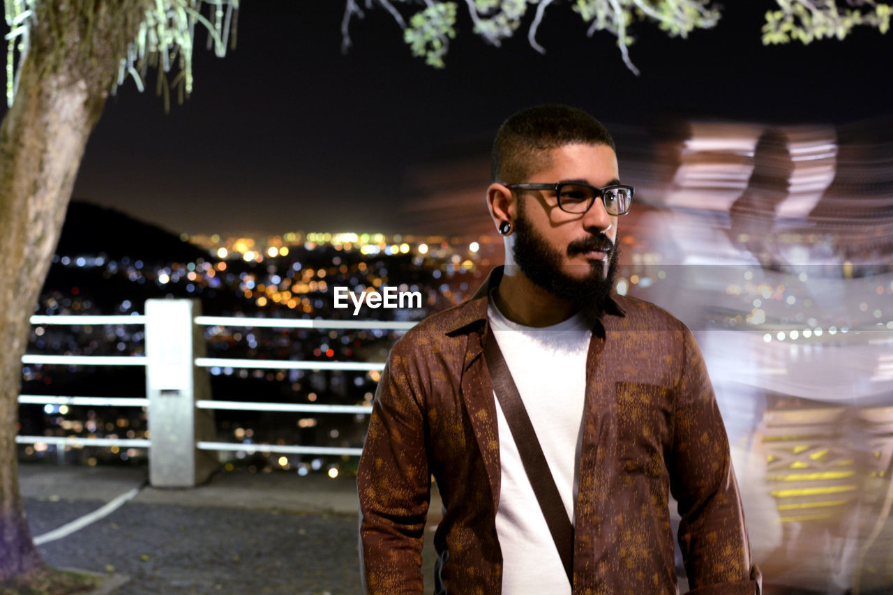 young adult, glasses, young men, front view, one person, waist up, eyeglasses, focus on foreground, real people, portrait, standing, beard, well-dressed, night, smiling, adult, facial hair, hairstyle