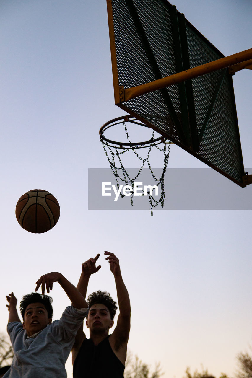 LOW ANGLE VIEW OF MEN PLAYING BASKETBALL AGAINST CLEAR SKY