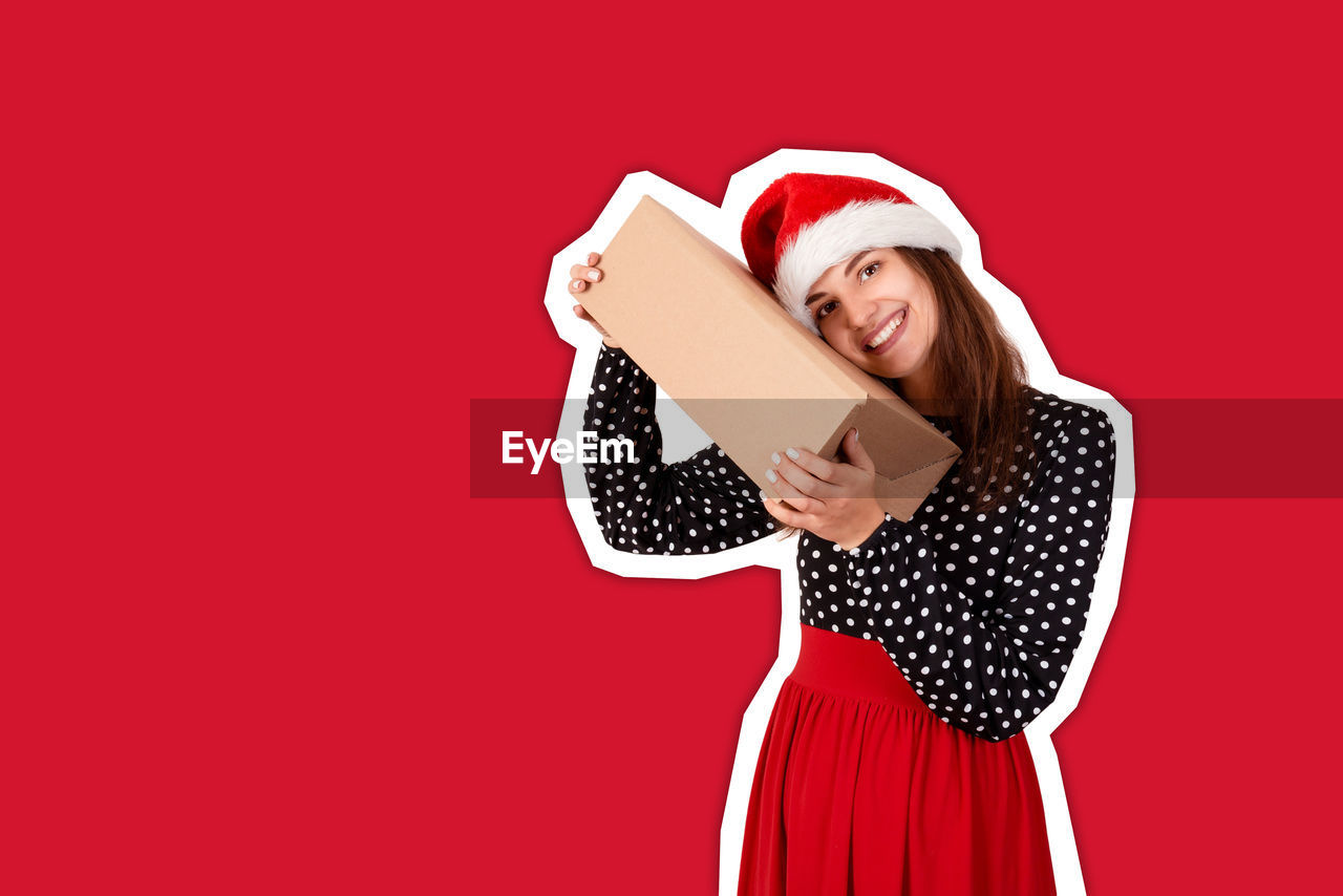 Portrait of smiling young woman holding gift box against red background