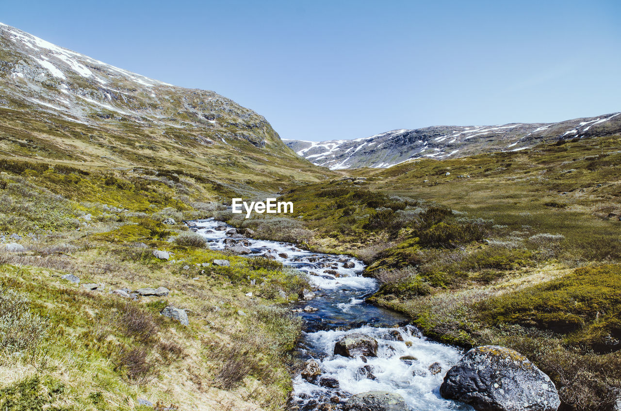 beauty in nature, sky, scenics - nature, mountain, nature, day, tranquility, non-urban scene, no people, landscape, environment, water, tranquil scene, rock, grass, clear sky, plant, idyllic, outdoors, flowing water, stream - flowing water, flowing