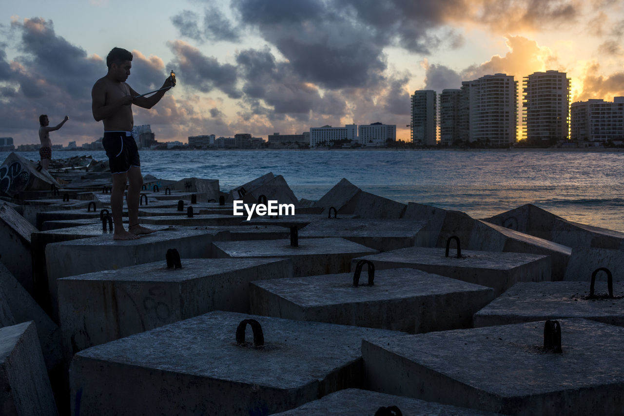 MAN STANDING ON BEACH BY BUILDINGS AGAINST SKY