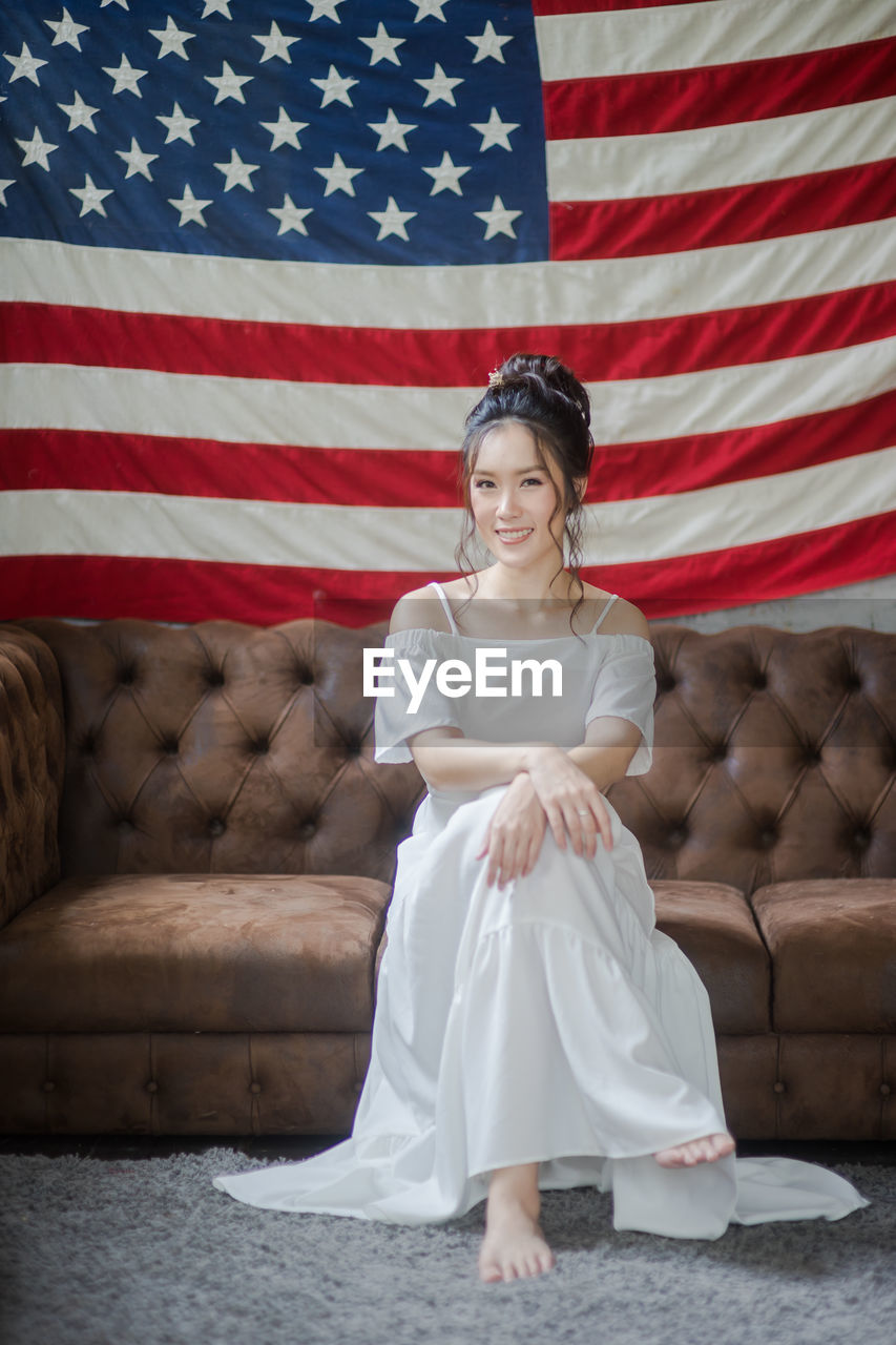 Portrait Of Smiling Young Woman Sitting On Sofa Against American Flag
