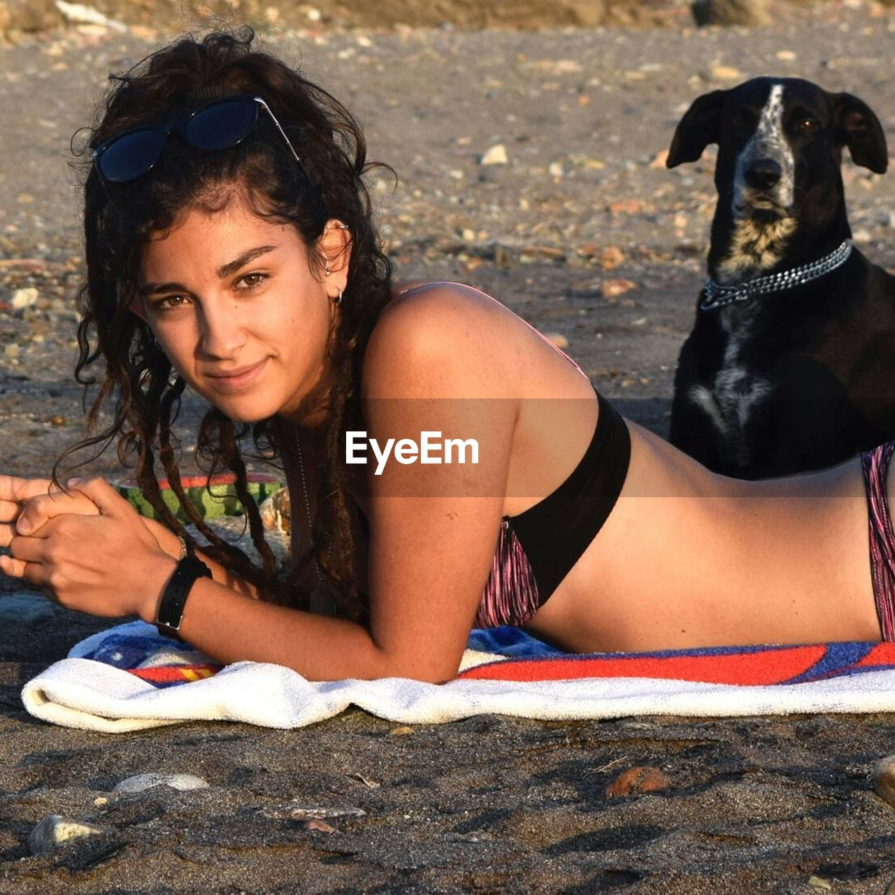Side view portrait of woman in bikini lying on towel by dog at beach