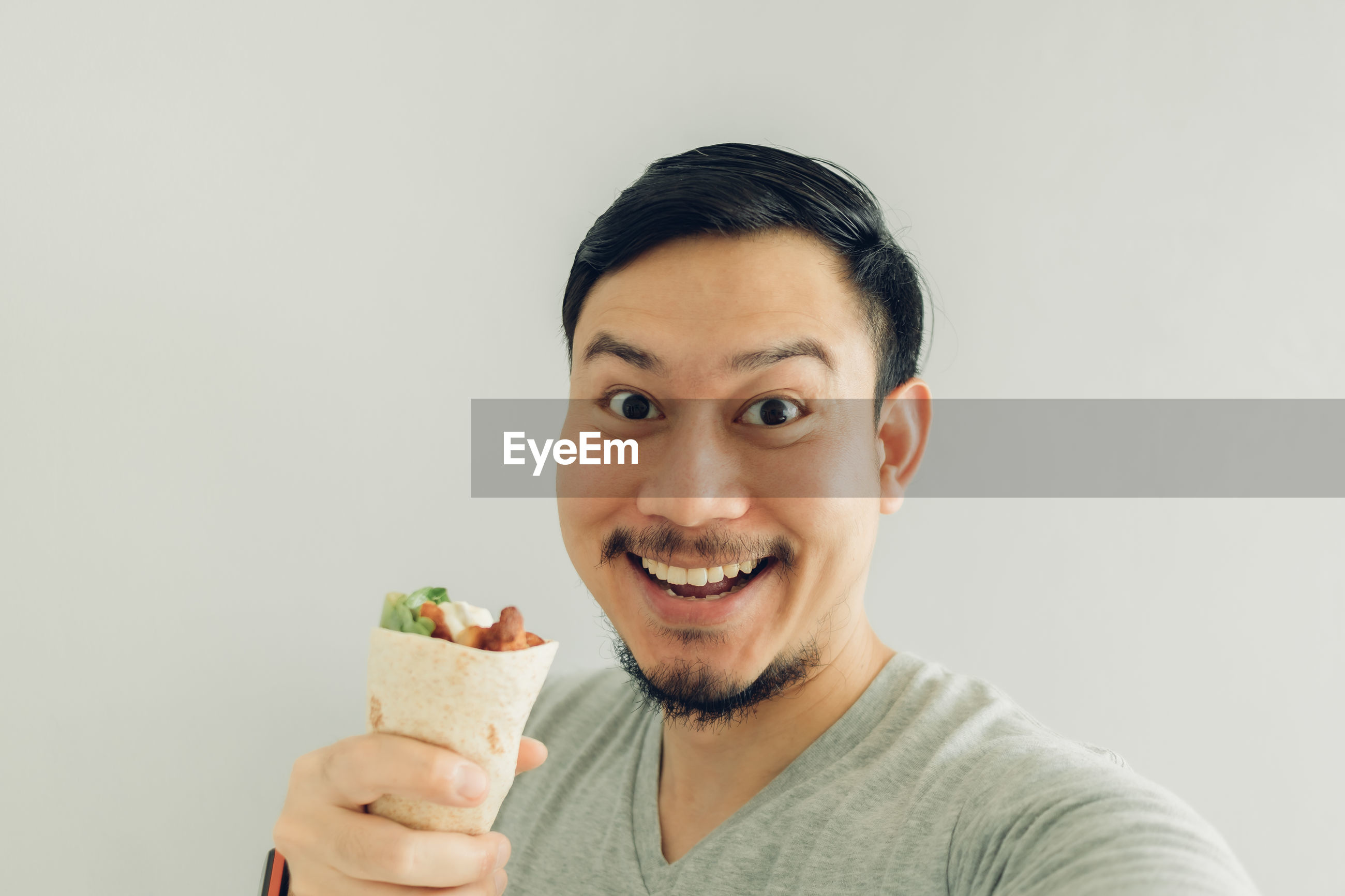 Portrait of man holding food against white background