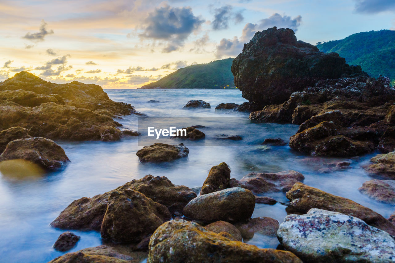 rock, water, rock - object, sea, solid, beauty in nature, sky, scenics - nature, cloud - sky, sunset, tranquility, nature, tranquil scene, beach, motion, land, rock formation, no people, idyllic, outdoors, horizon over water, rocky coastline
