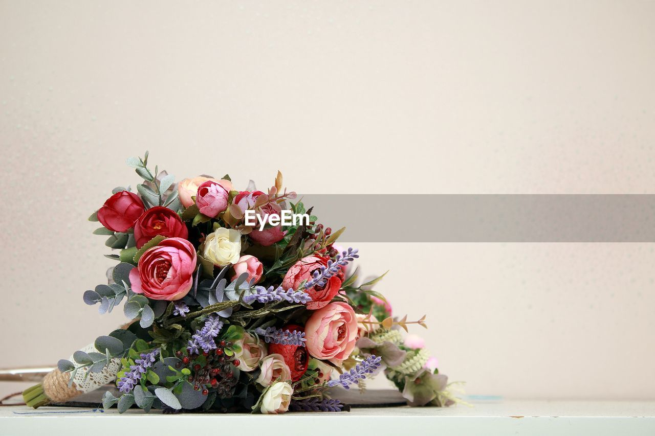 Close-up of rose bouquet on table against white background