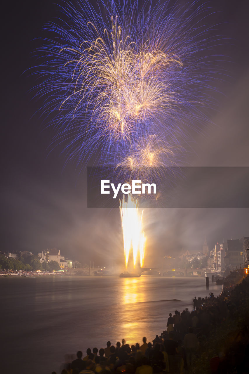 firework, illuminated, sky, motion, night, arts culture and entertainment, water, architecture, firework display, exploding, nature, building exterior, celebration, event, long exposure, city, built structure, sea, firework - man made object, no people, cityscape, outdoors, sparks