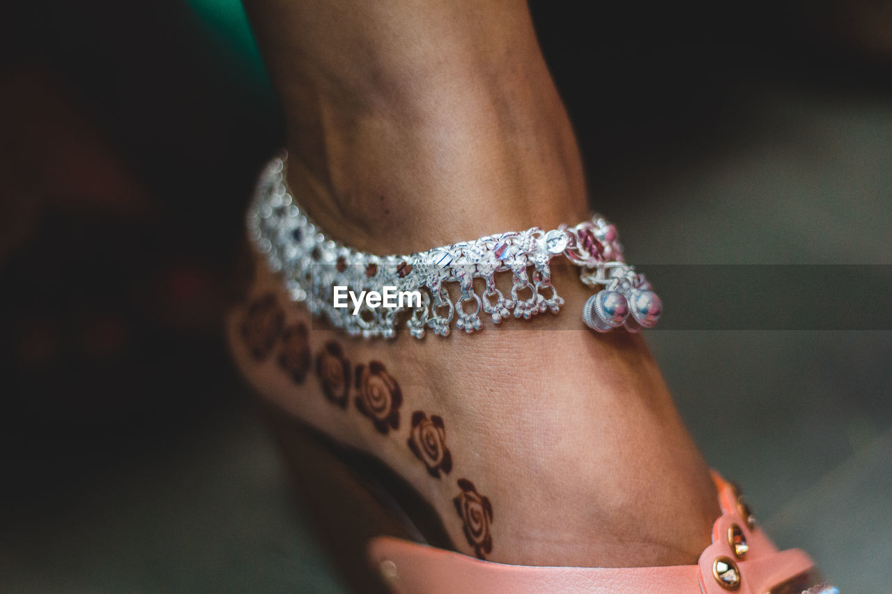 human body part, one person, jewelry, body part, women, focus on foreground, close-up, midsection, real people, lifestyles, adult, human hand, bracelet, fashion, hand, leisure activity, selective focus, human leg, tattoo, personal accessory, human limb, luxury, floral pattern