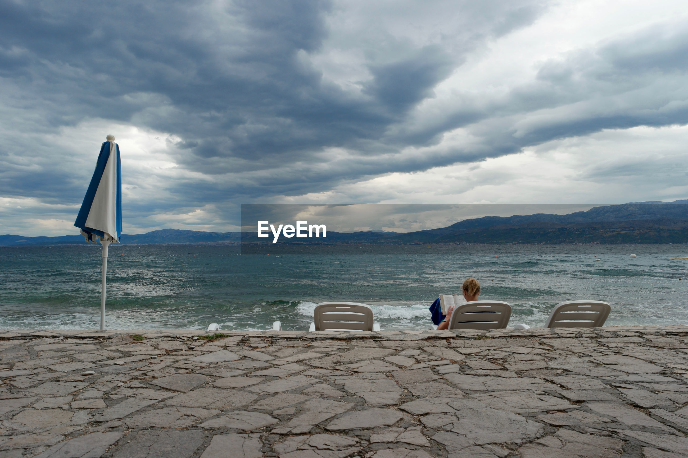 Rear view of woman reading book while sitting on deck chair at beach against cloudy sky