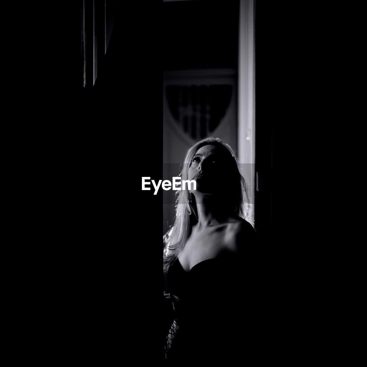 Mid Adult Woman Looking Up While Standing At Doorway In Darkroom