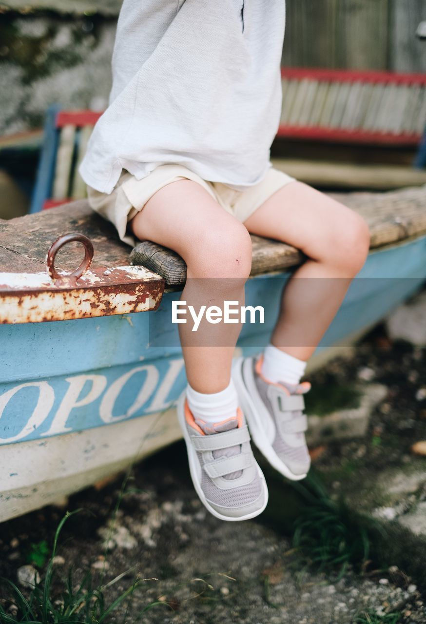 real people, one person, low section, human body part, human leg, day, body part, lifestyles, sitting, focus on foreground, child, childhood, women, outdoors, leisure activity, shoe, nature, casual clothing, females, human foot, shorts, human limb