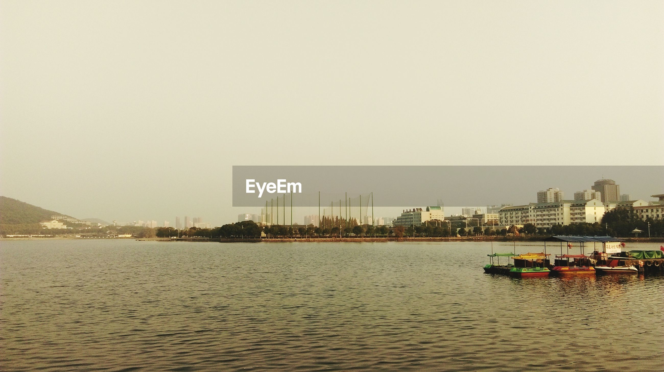 clear sky, water, copy space, architecture, built structure, building exterior, waterfront, nautical vessel, river, transportation, city, sea, boat, tranquility, nature, incidental people, travel destinations, scenics, mode of transport, tranquil scene
