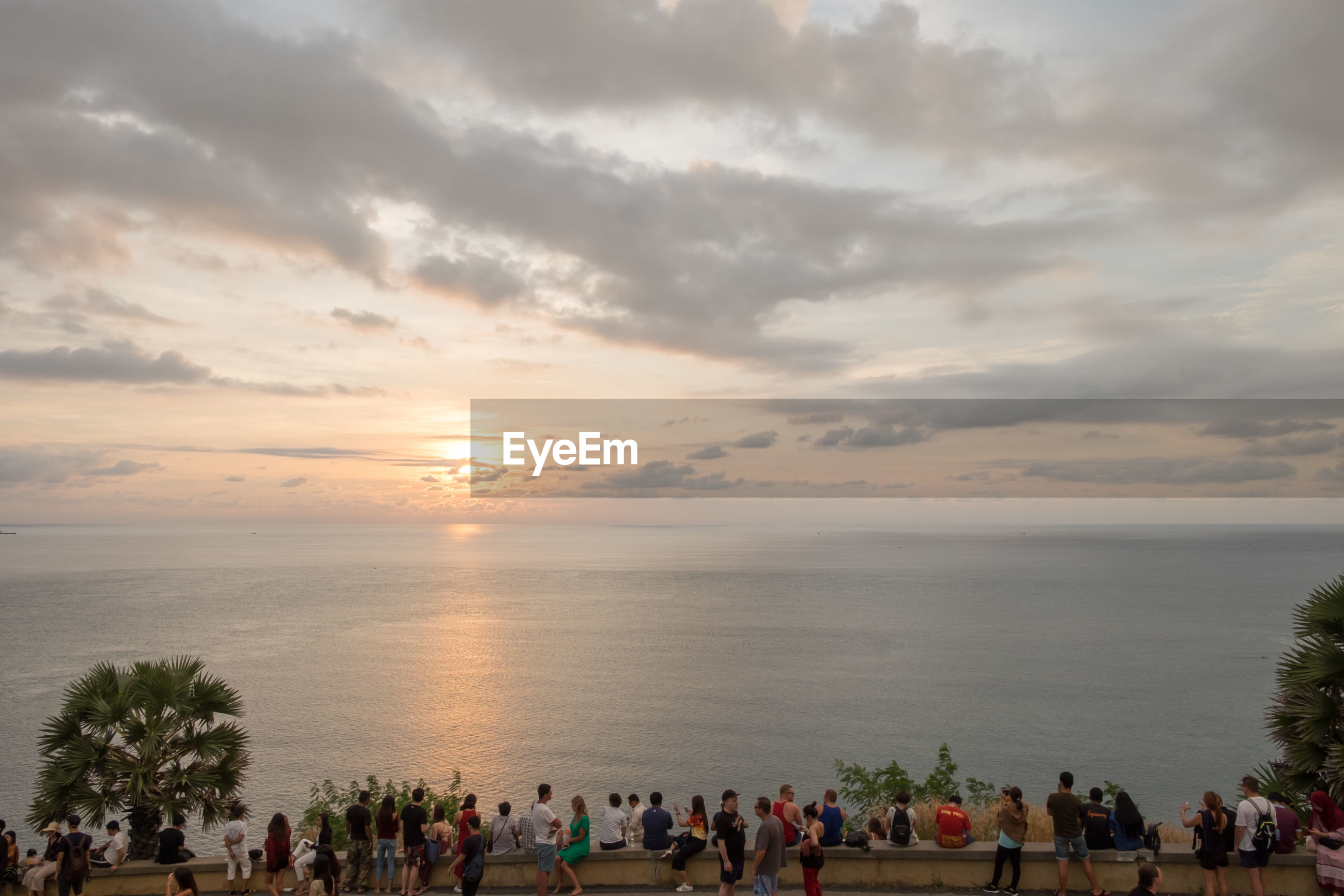 People bu sea against cloudy sky during sunset