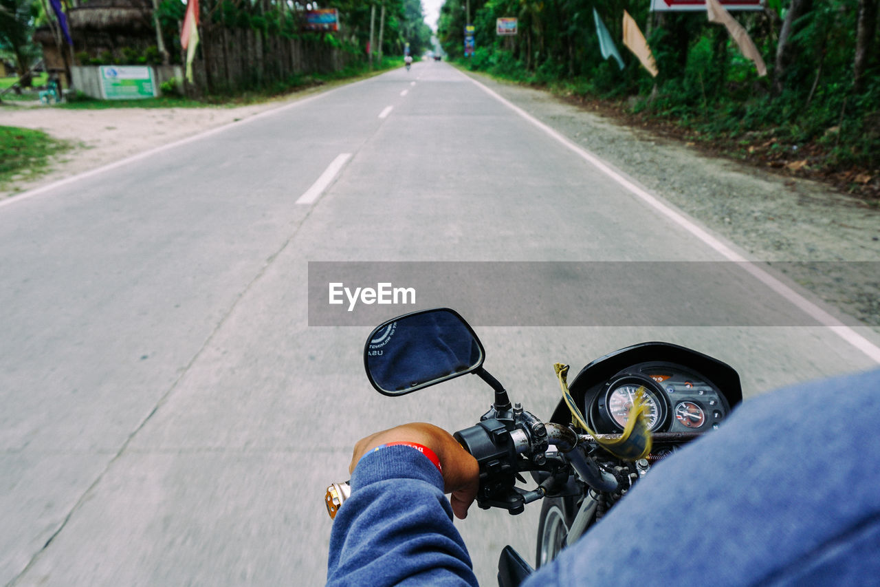 Midsection of man riding motorcycle on road