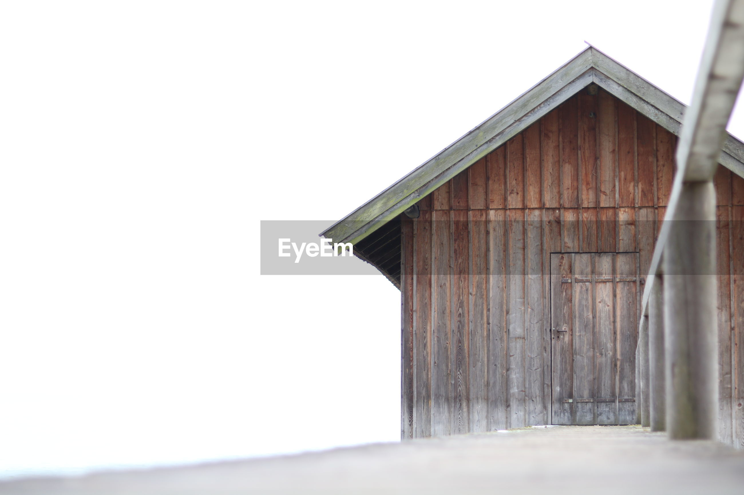 WOODEN HUT BY BARN AGAINST SKY