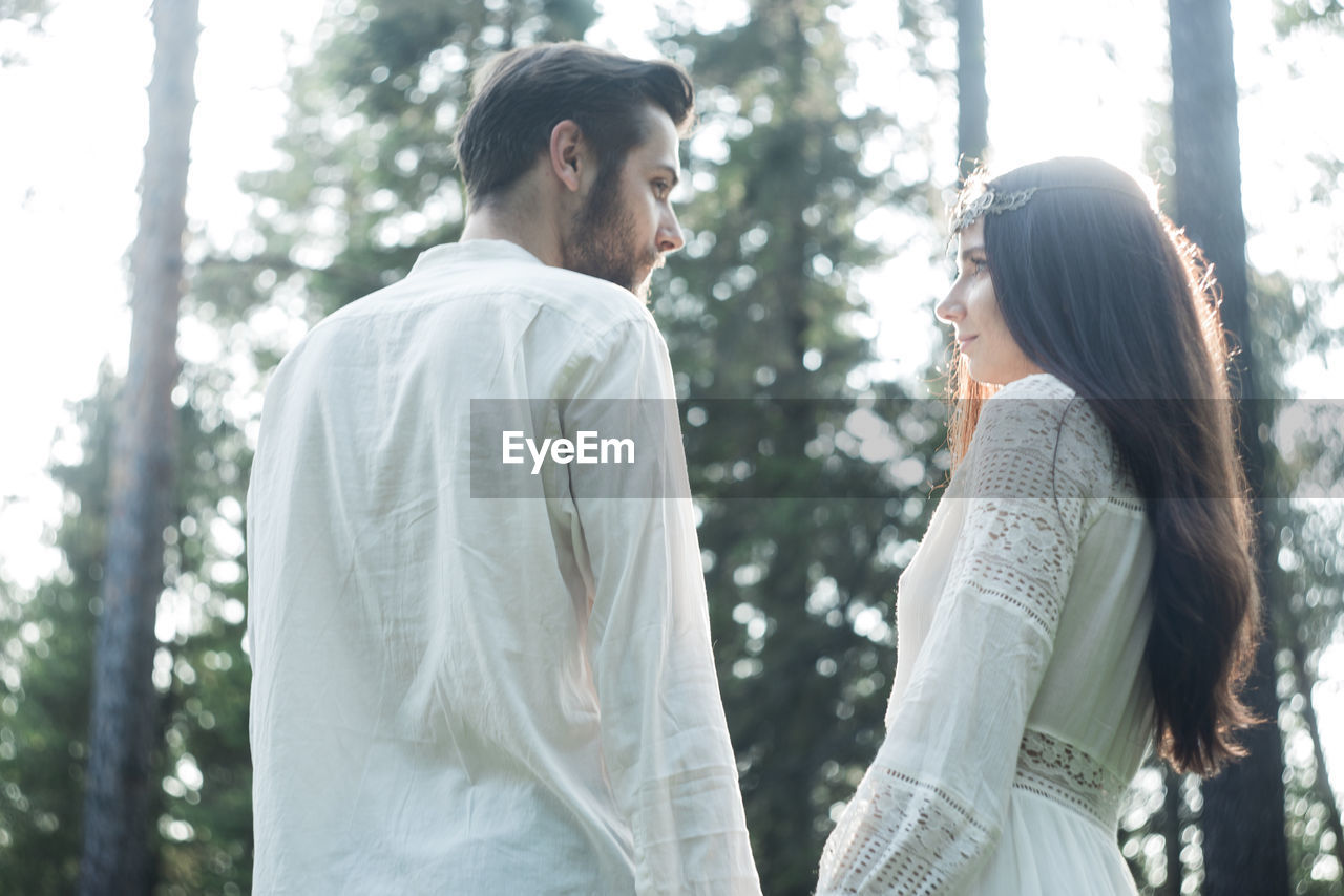 Romantic couple standing in forest