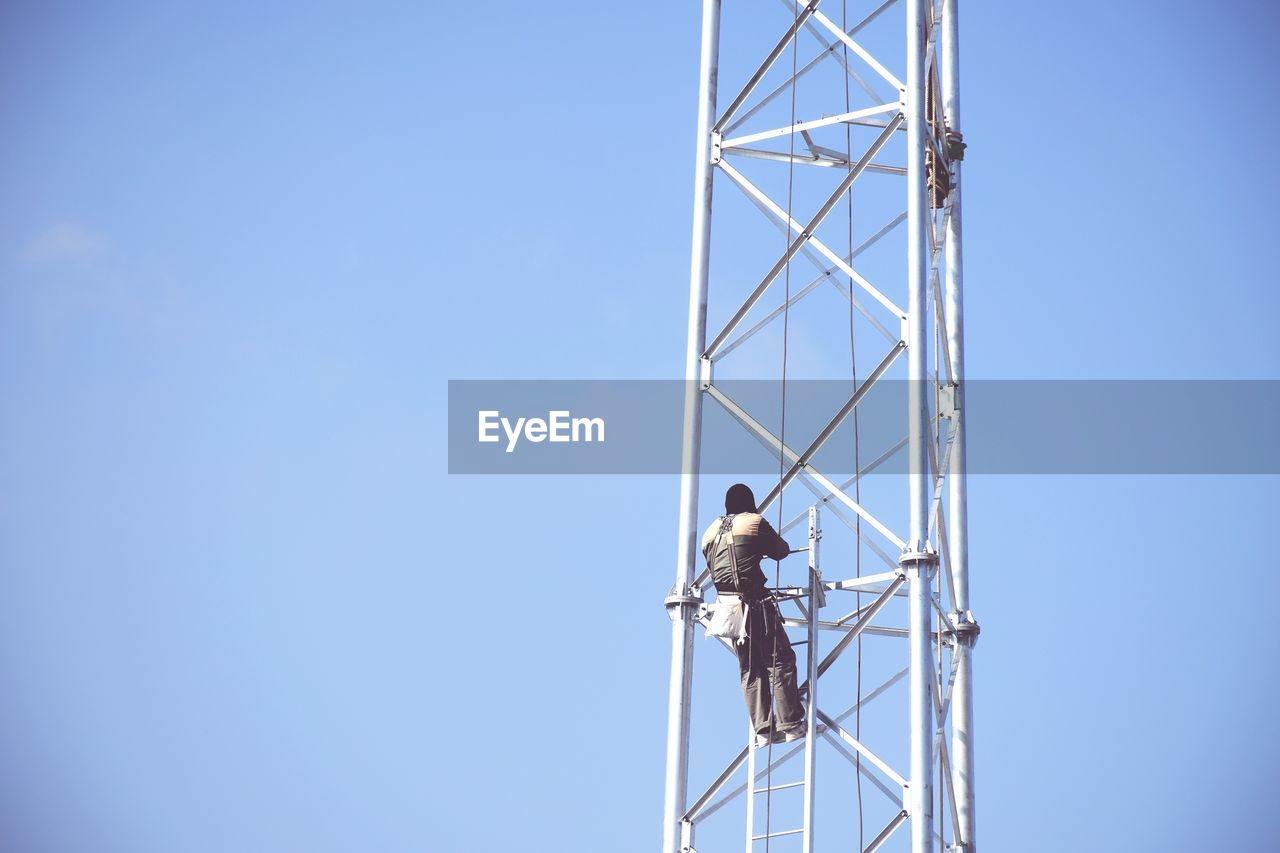 Rear view of worker on pole against blue sky