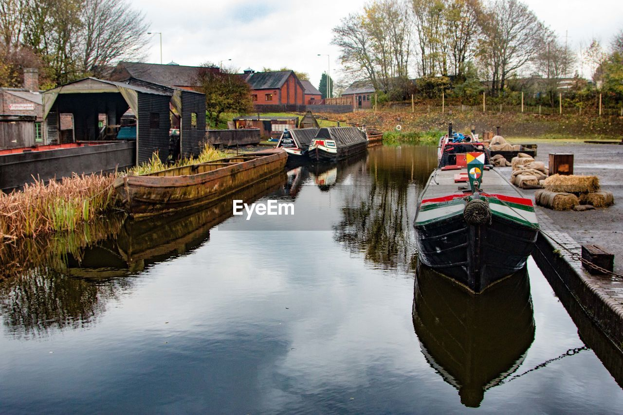 water, built structure, architecture, building exterior, nautical vessel, day, canal, reflection, outdoors, transportation, moored, lake, no people, nature, tree, sky
