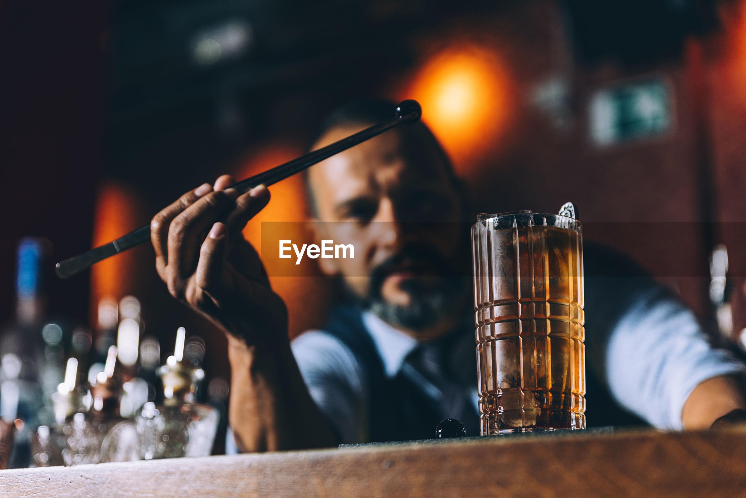 Bartender making drink at counter