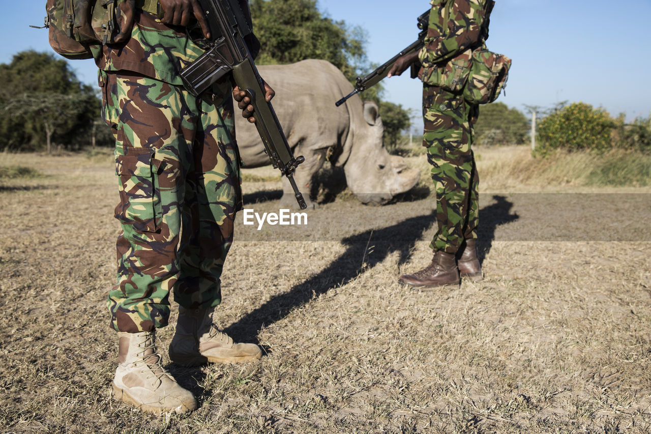 Soldiers Standing By Rhinoceros On Field