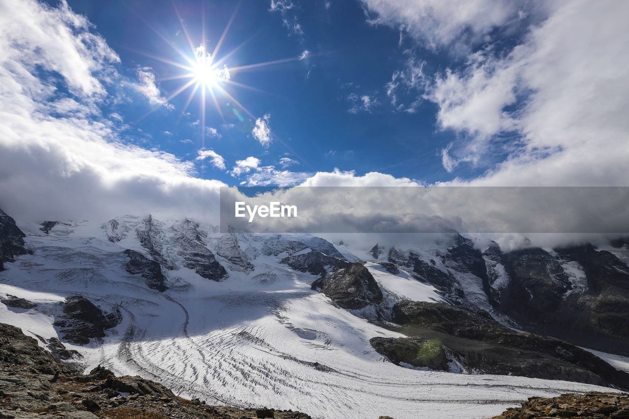 sky, snow, cold temperature, cloud - sky, beauty in nature, scenics - nature, winter, mountain, tranquil scene, tranquility, snowcapped mountain, sunlight, sunbeam, nature, non-urban scene, sun, mountain range, covering, environment, lens flare, no people, bright