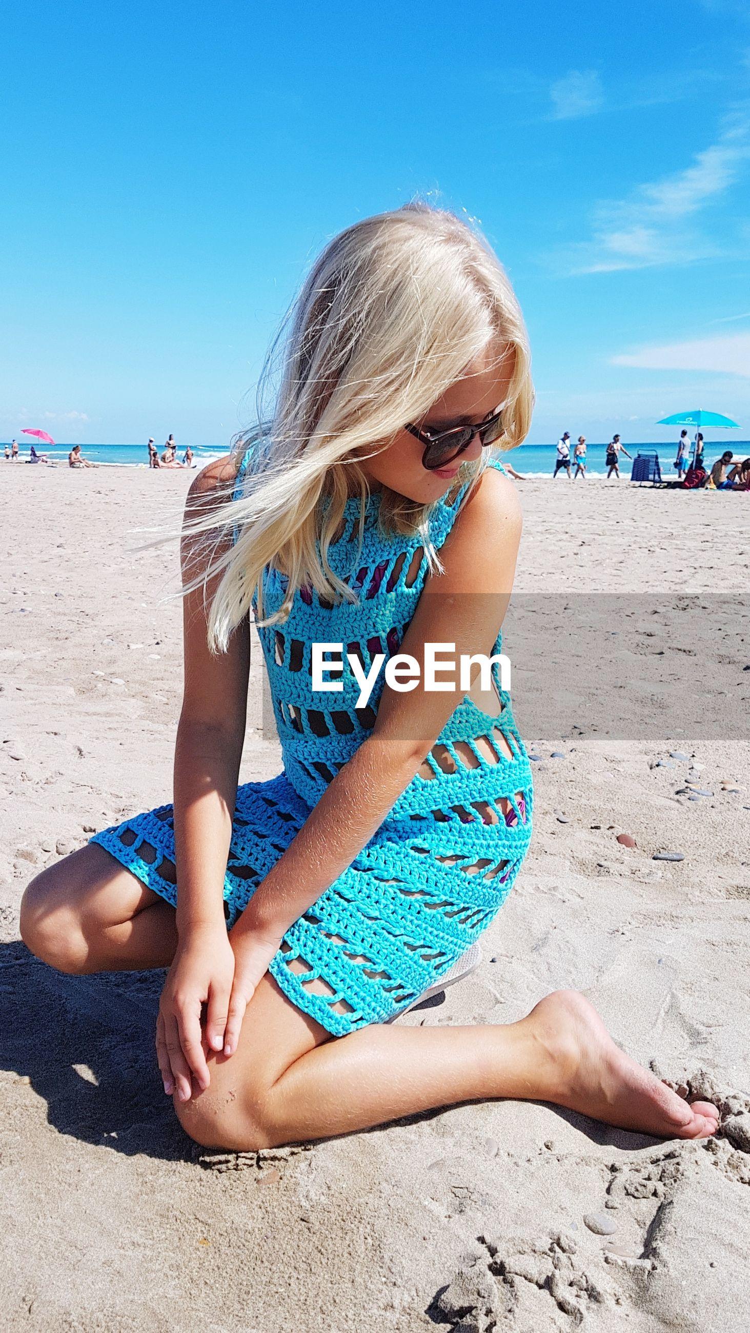 Girl in blue dress sitting at beach