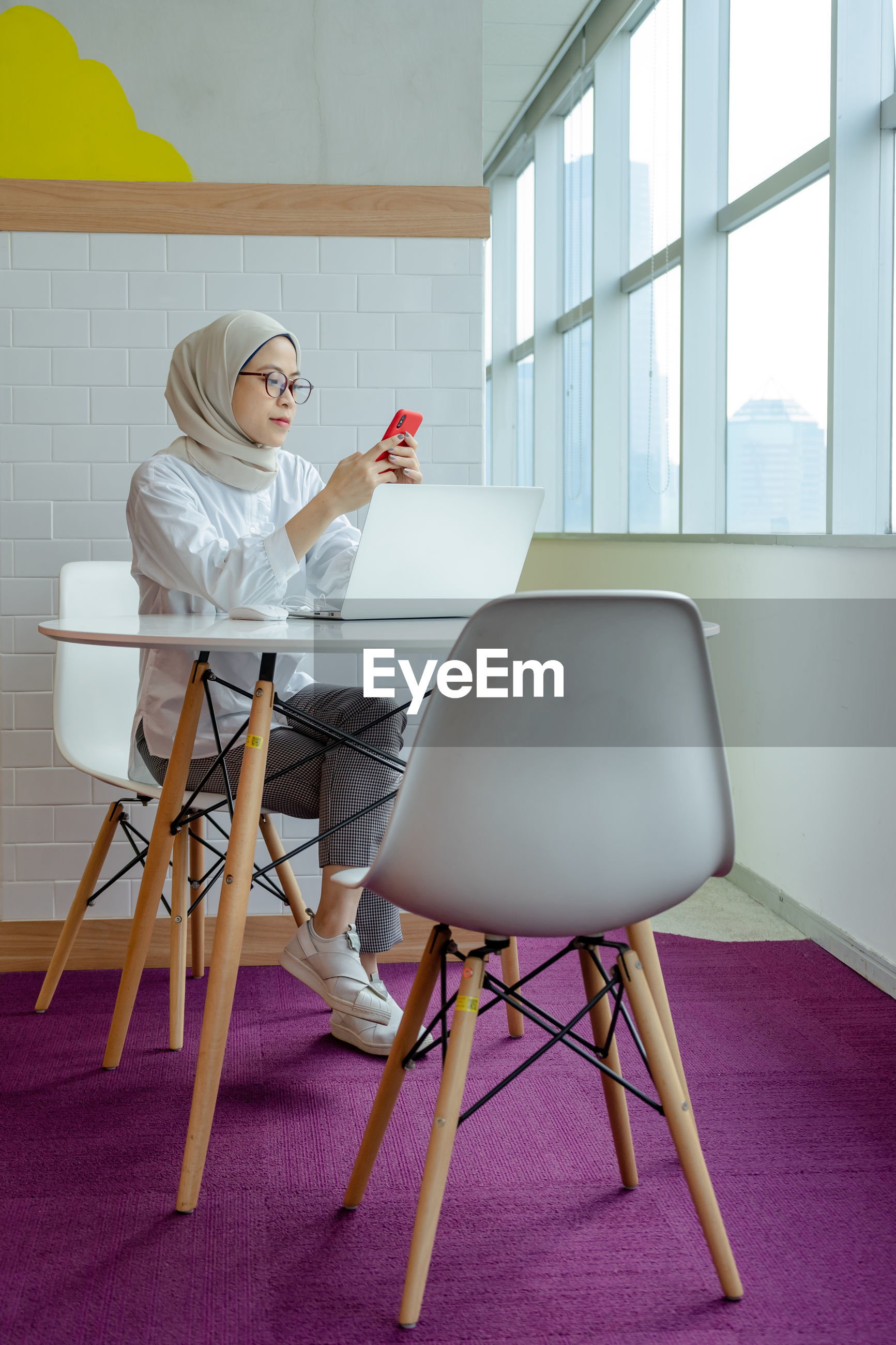 WOMAN USING PHONE WHILE SITTING ON CHAIR IN OFFICE