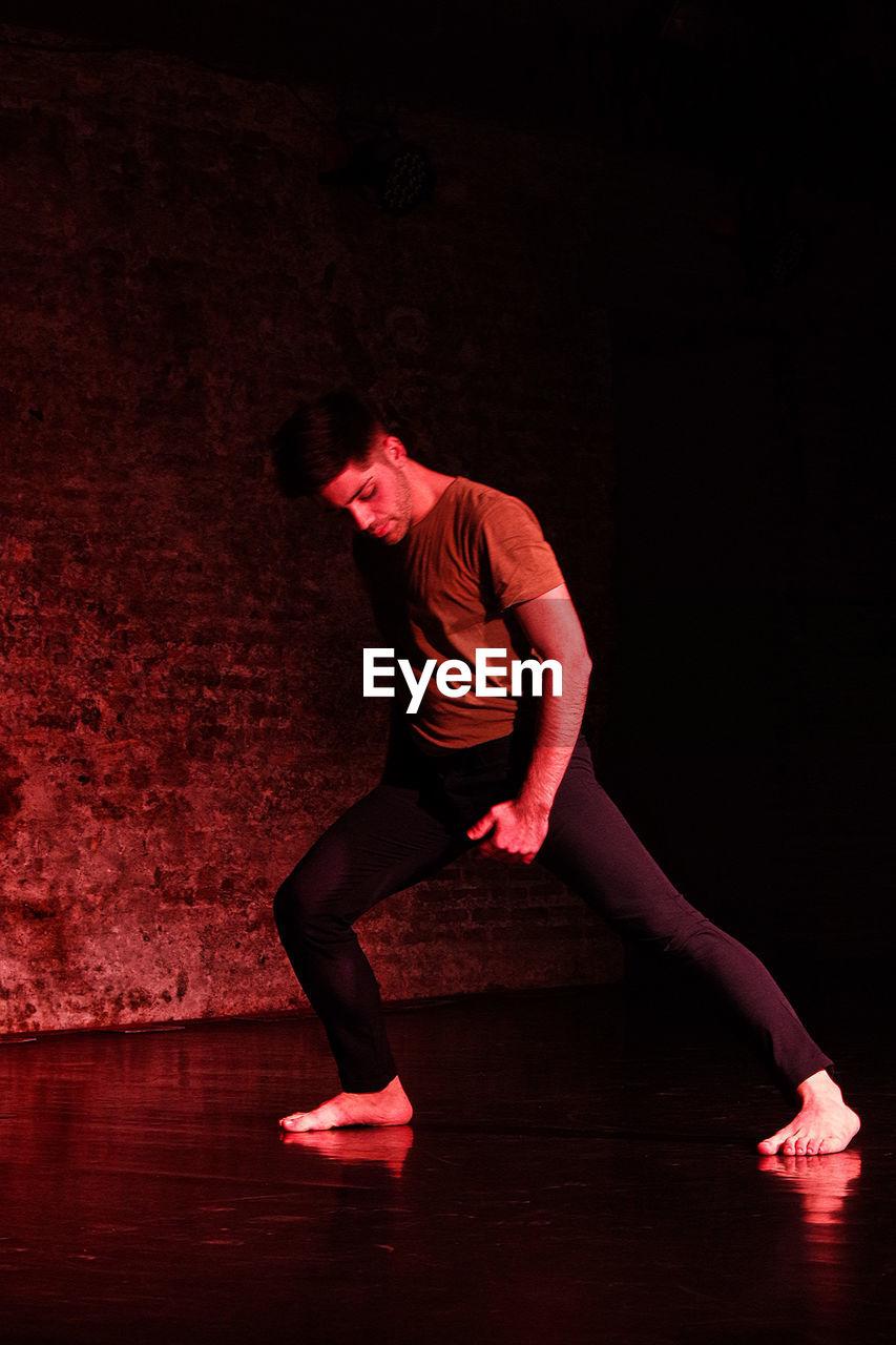 Full Length Of Man Dancing Against Wall