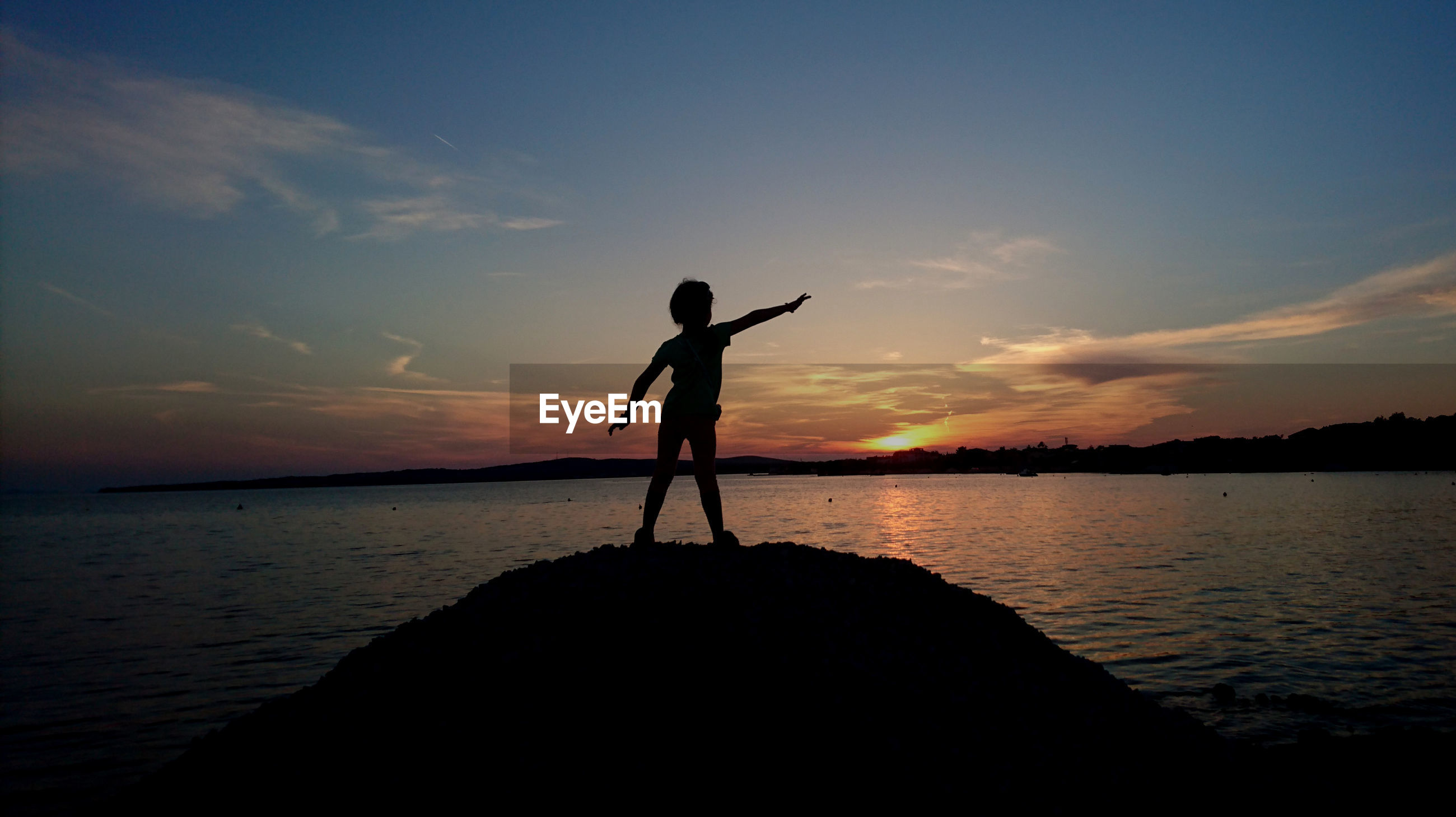 SILHOUETTE BOY STANDING ON BEACH AGAINST SKY AT SUNSET
