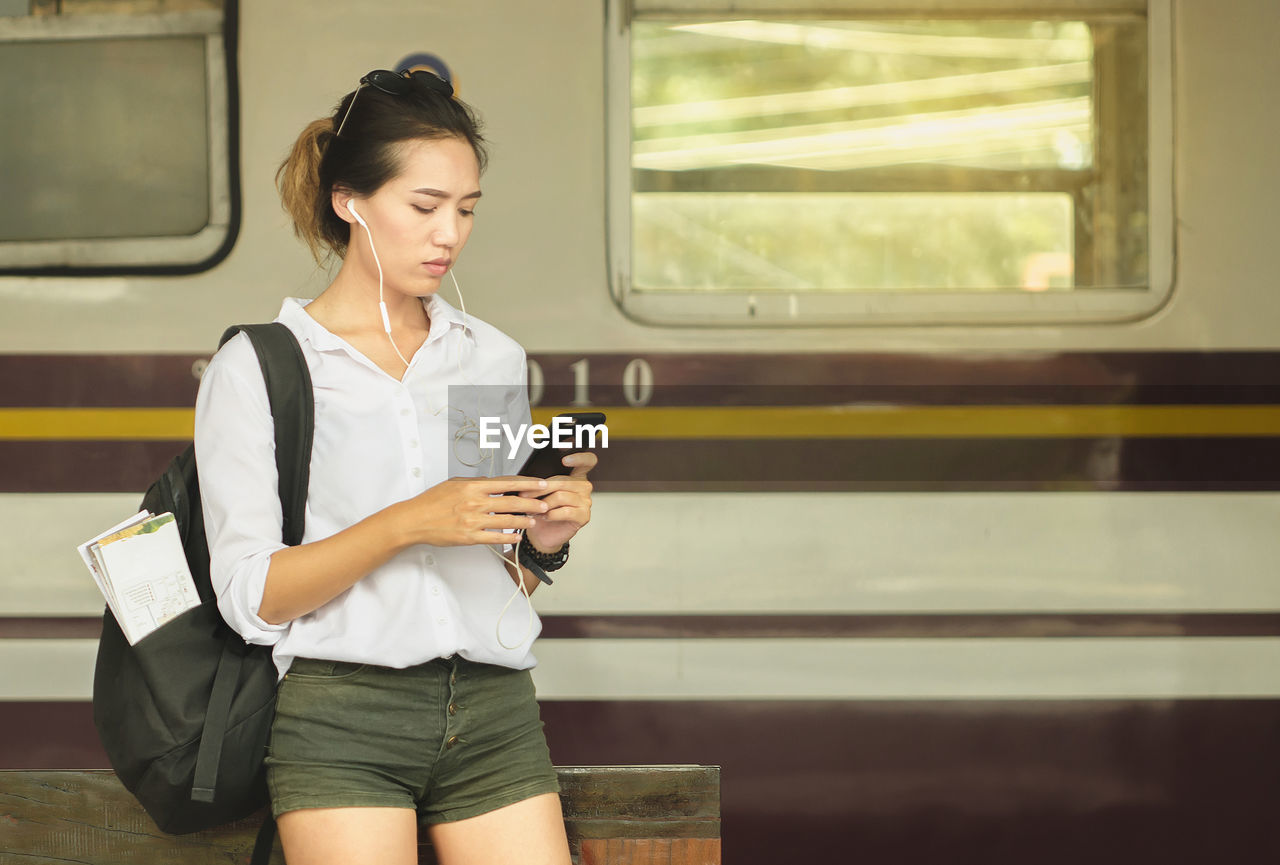 Young woman using mobile phone while standing against train at railroad platform
