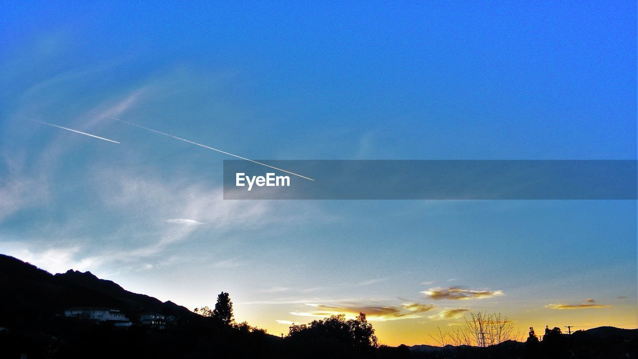 vapor trail, contrail, blue, beauty in nature, sky, scenics, nature, low angle view, no people, silhouette, outdoors, sunset, day