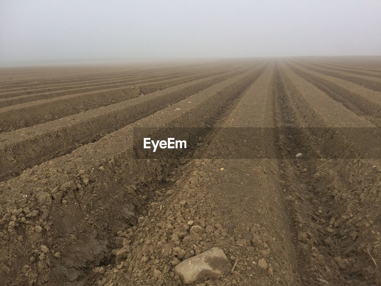 View Of Plowed Landscape Against Sky