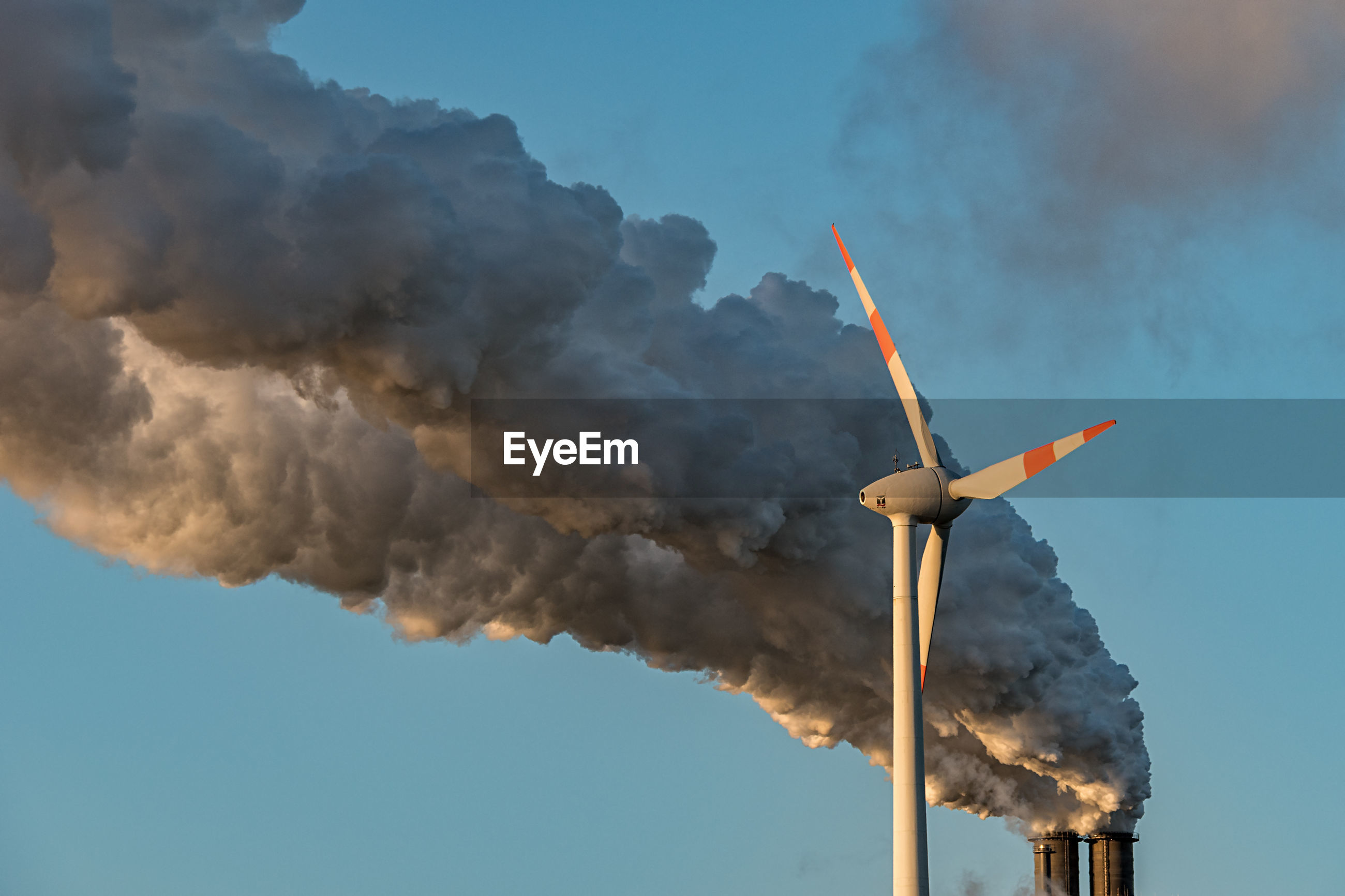 Low angle view of wind turbine by smoke emitting from chimney against blue sky