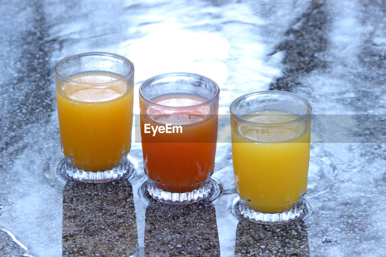 High Angle View Of Various Juice Glasses On Granite Counter