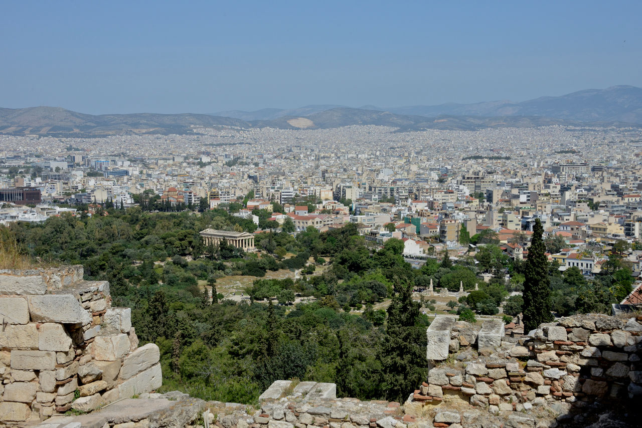 architecture, building exterior, built structure, city, sky, cityscape, residential district, building, mountain, nature, town, clear sky, travel destinations, day, crowded, history, the past, outdoors, townscape, ancient civilization, stone wall