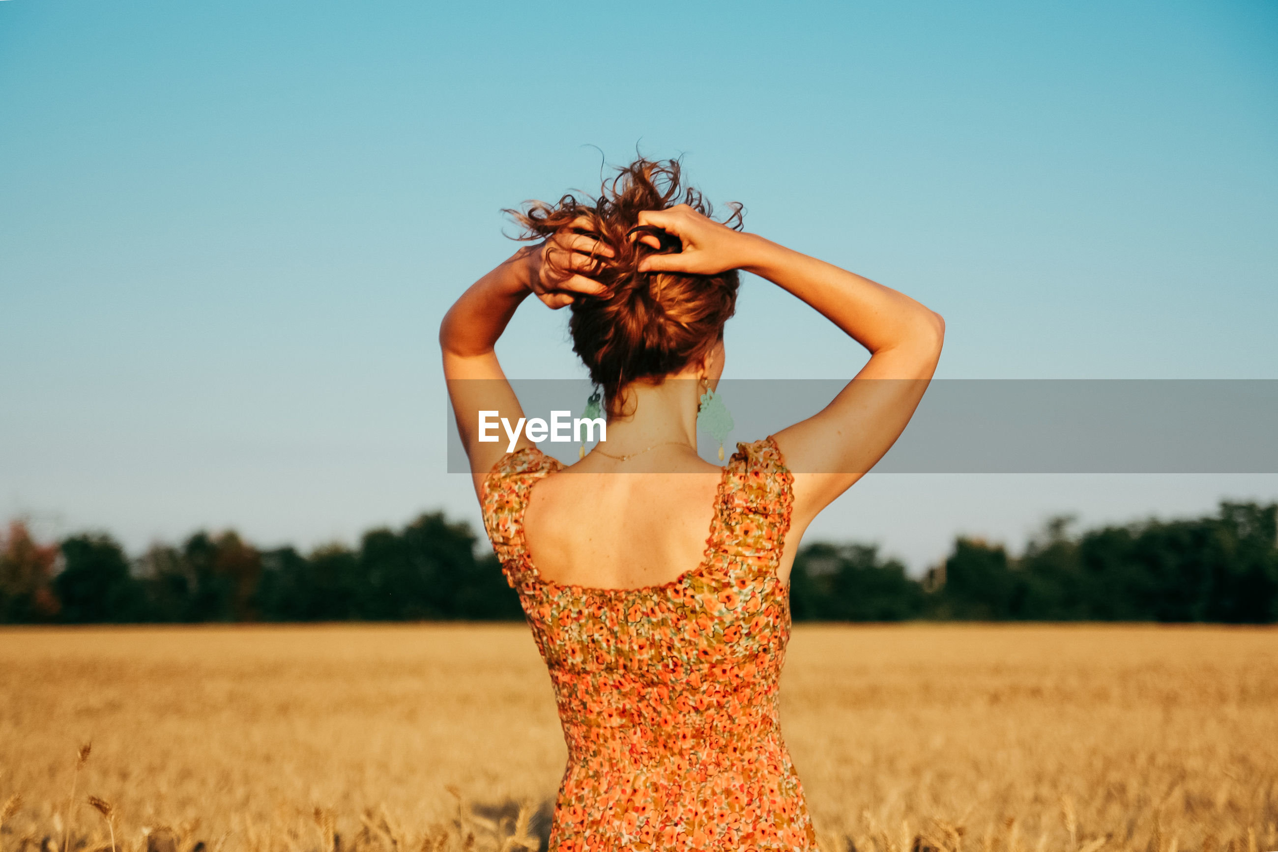 Young woman against clear sky on field