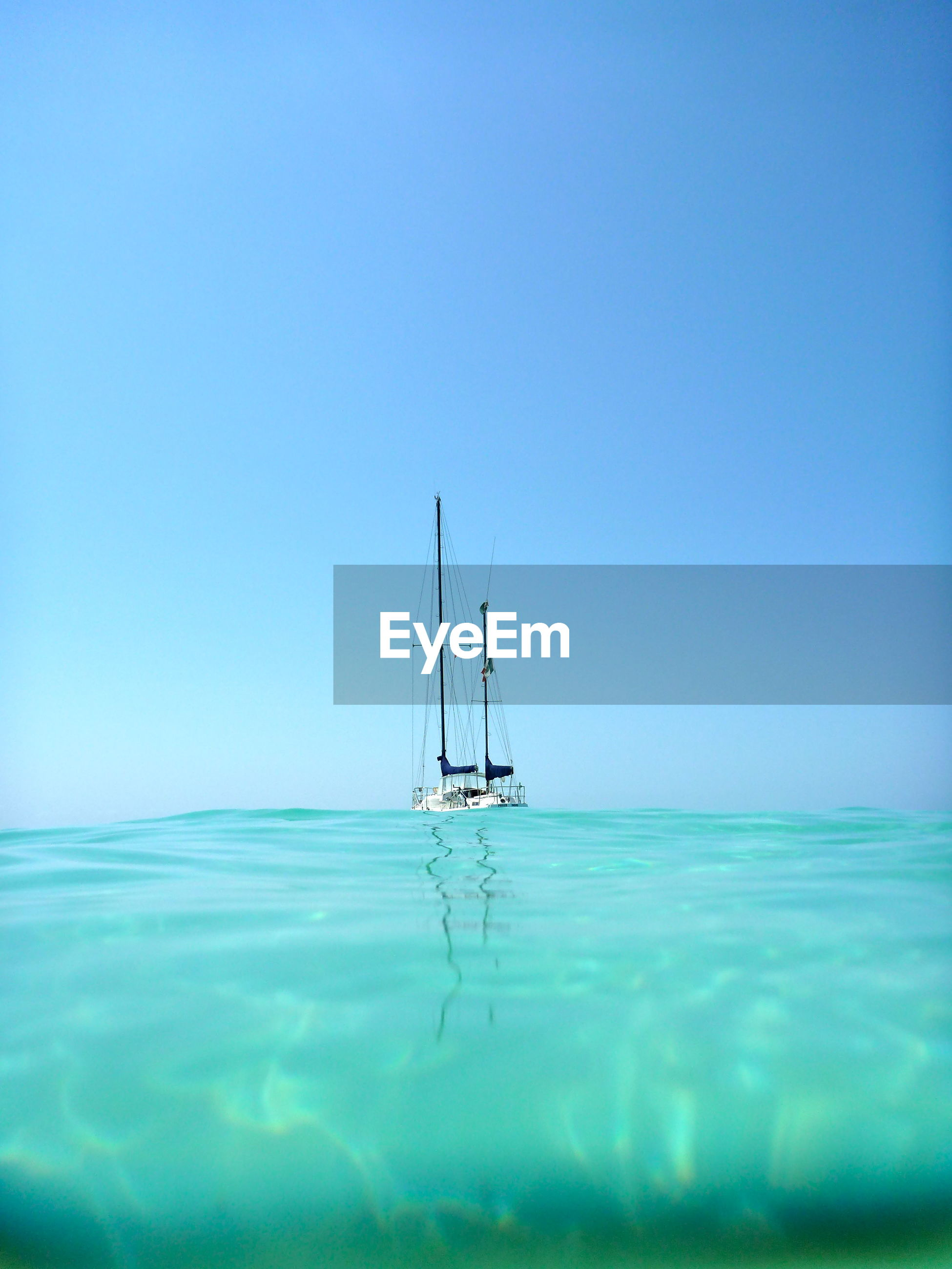 SAILBOAT IN SEA AGAINST BLUE SKY