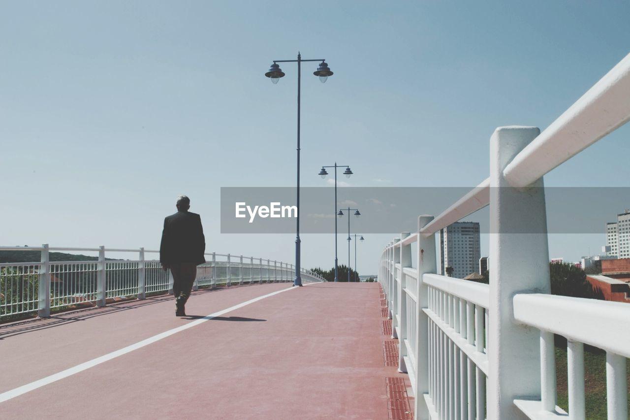Rear view of man walking on bridge against clear sky
