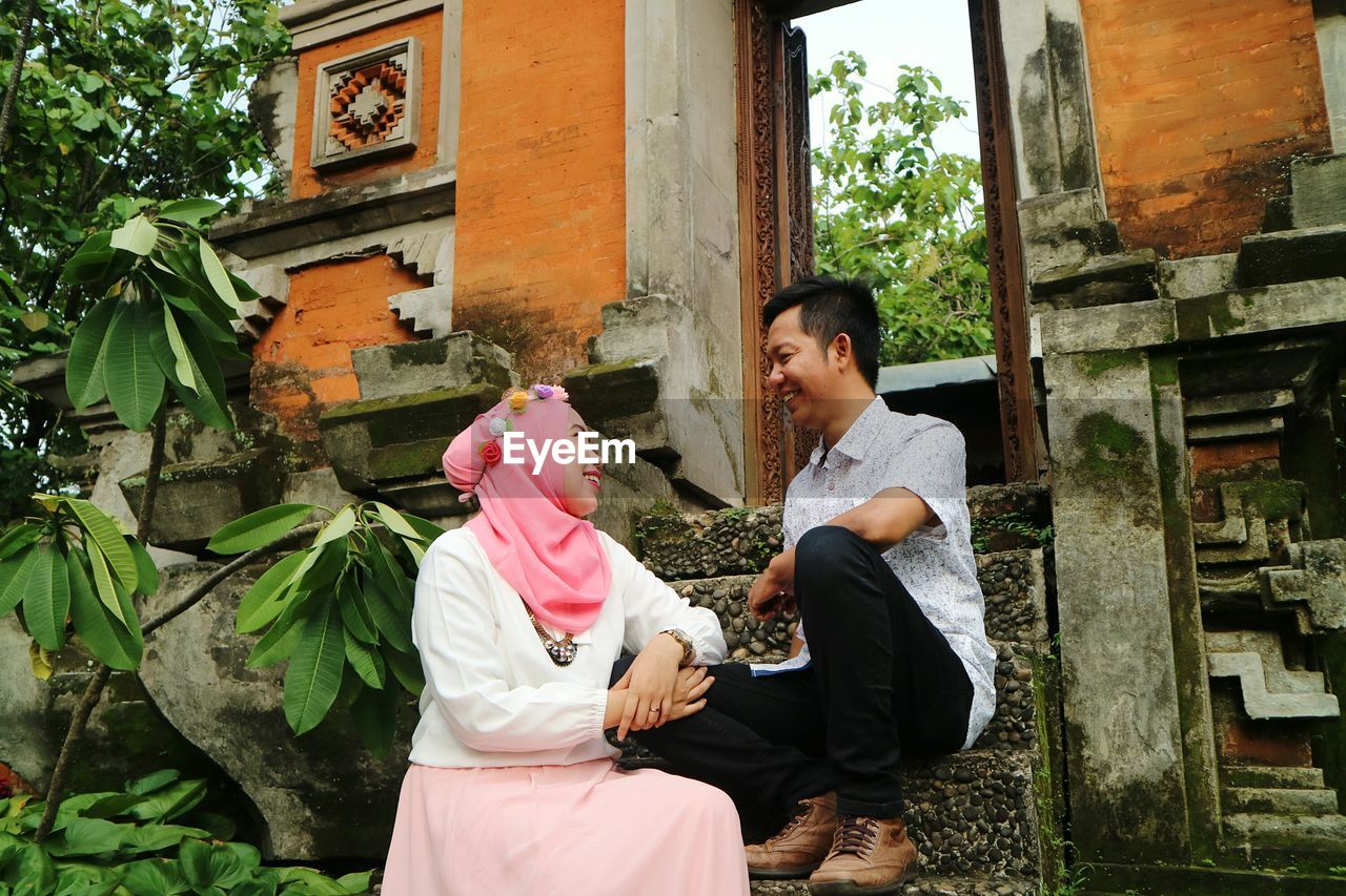Low angle view of smiling couple looking at each other while sitting on steps