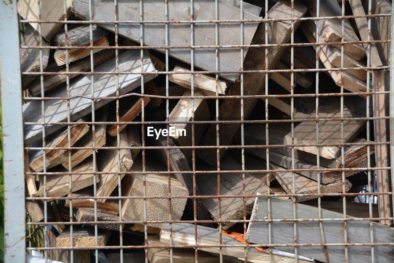Abandoned Wooden Planks Seen Through Fence
