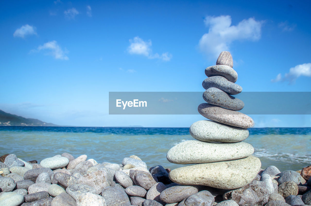 sea, stack, balance, rock - object, pebble, nature, tranquil scene, stone - object, tranquility, cloud - sky, scenics, day, beauty in nature, water, sky, horizon over water, beach, outdoors, no people, blue, sunlight