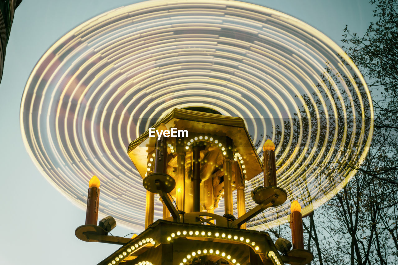Low Angle View Of Illuminated Wheel Spinning At Market